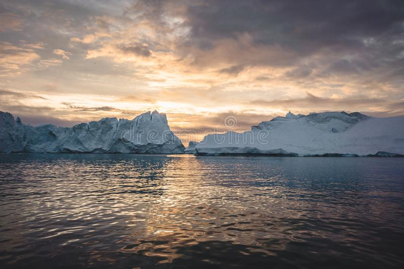 Arctic nature landscape with icebergs in Greenland icefjord with midnight sun sunset sunrise in the horizon. Early stock photo