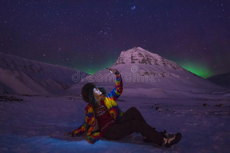 Arctic Northern lights aurora borealis sky star in Norway travel blogger girl man Svalbard in Longyearbyen city the moon mountains stock image