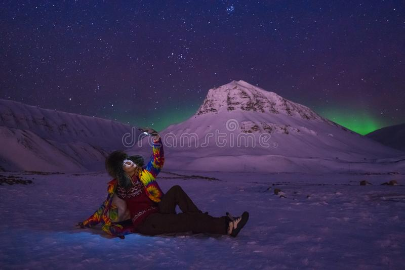 Arctic Northern lights aurora borealis sky star in Norway travel blogger girl man Svalbard in Longyearbyen city the moon mountains stock photo