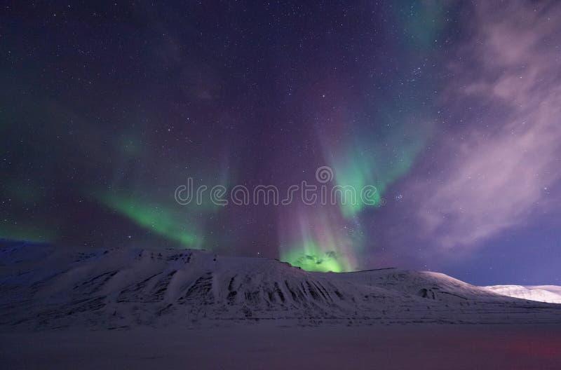 Arctic Northern lights aurora borealis sky star in Norway travel Svalbard in Longyearbyen city the moon mountains. The polar arctic Northern lights aurora stock photo