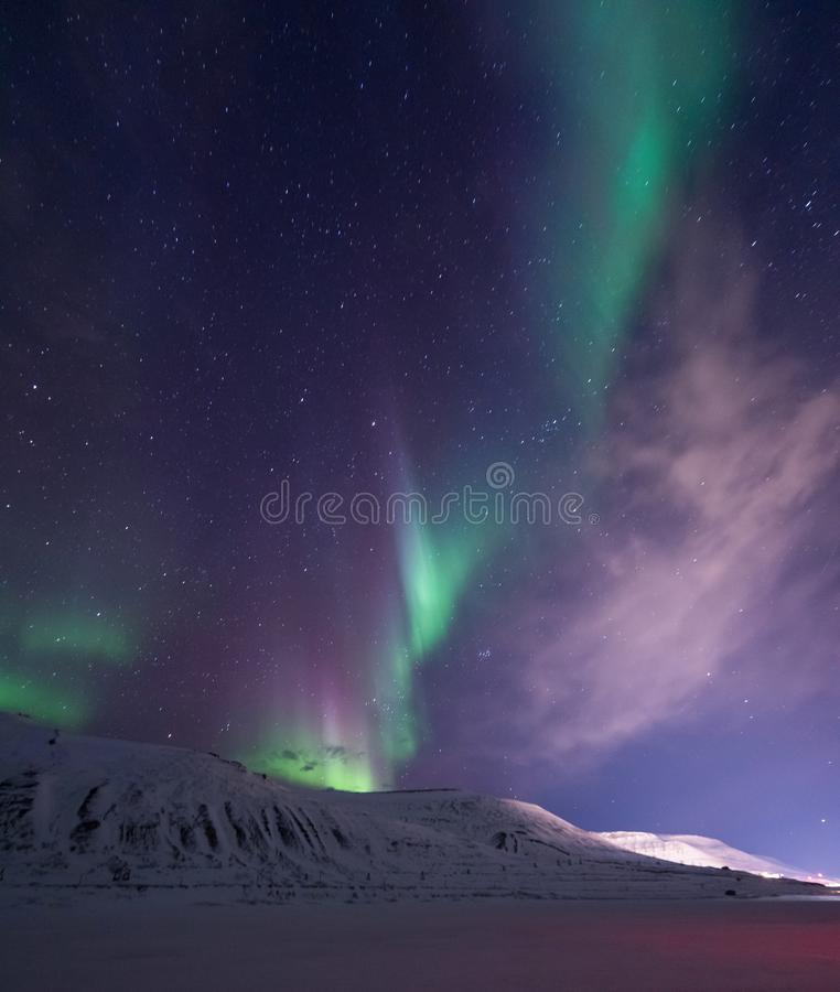 Arctic Northern lights aurora borealis sky star in Norway travel Svalbard in Longyearbyen city the moon mountains. The polar arctic Northern lights aurora royalty free stock photography