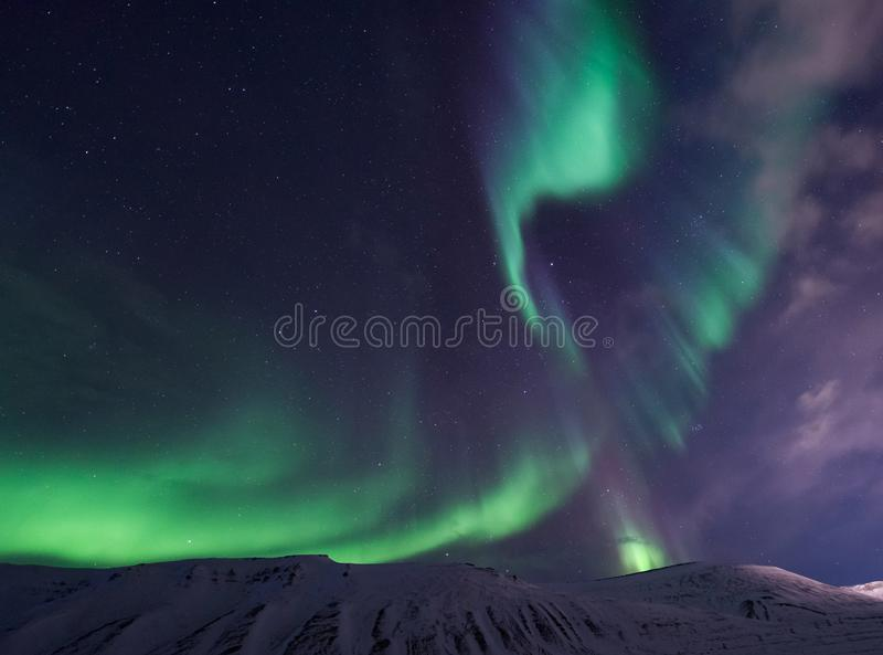 Arctic Northern lights aurora borealis sky star in Norway travel Svalbard in Longyearbyen city the moon mountains. The polar arctic Northern lights aurora stock image