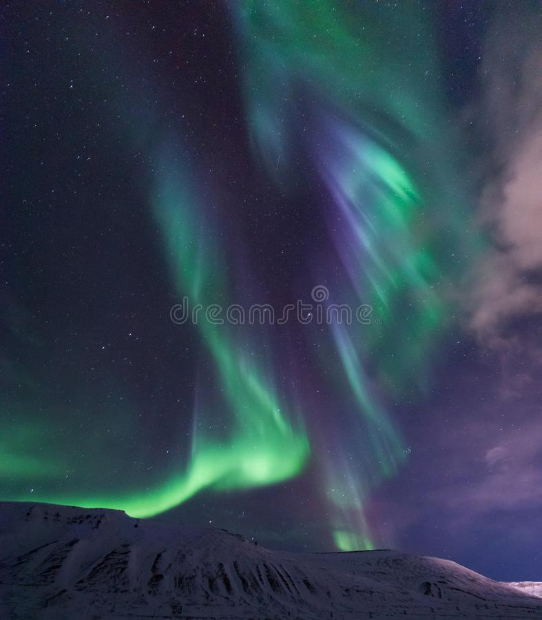 Arctic Northern lights aurora borealis sky star in Norway travel Svalbard in Longyearbyen city the moon mountains royalty free stock photo