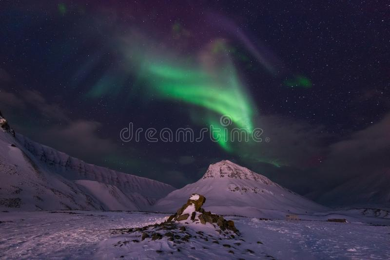 Arctic Northern lights aurora borealis sky star in Norway travel Svalbard in Longyearbyen city the moon mountains. The polar arctic Northern lights aurora royalty free stock images