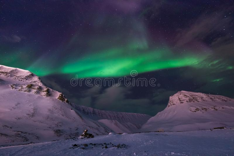 Arctic Northern lights aurora borealis sky star in Norway travel Svalbard in Longyearbyen city the moon mountains stock image