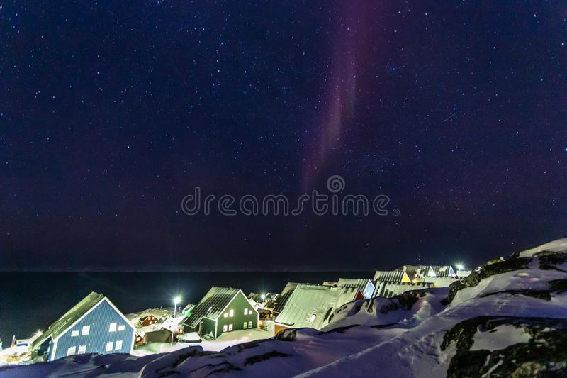 Arctic polar night over colorful inuit houses with small northern light in a suburb of arctic capital Nuuk, Greenland stock images