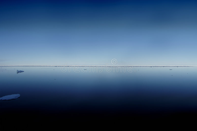 Arctic sea on a sunny day. With the horizon visible and deep pastel blue sea and sky royalty free stock photos
