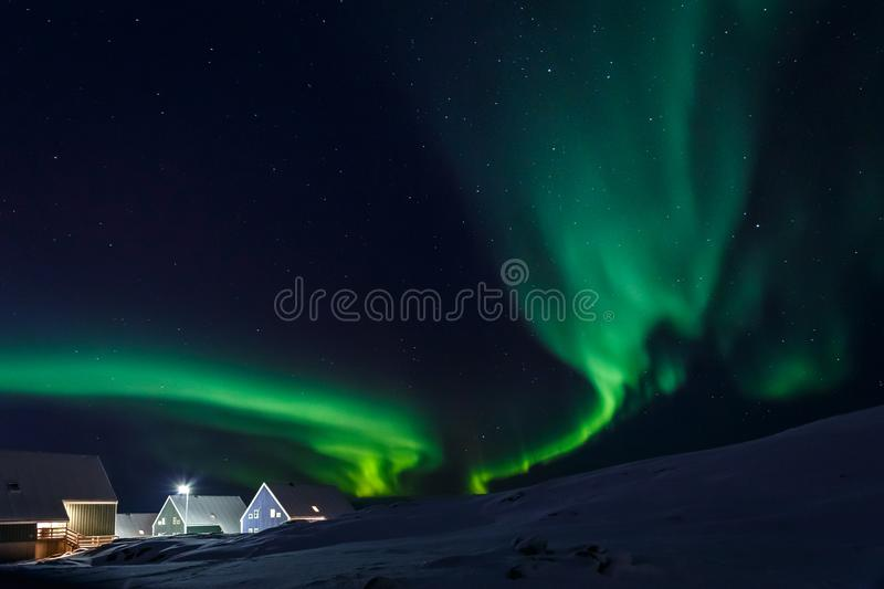 Arctic village and green waves of Northern lights in a suburb of stock photo