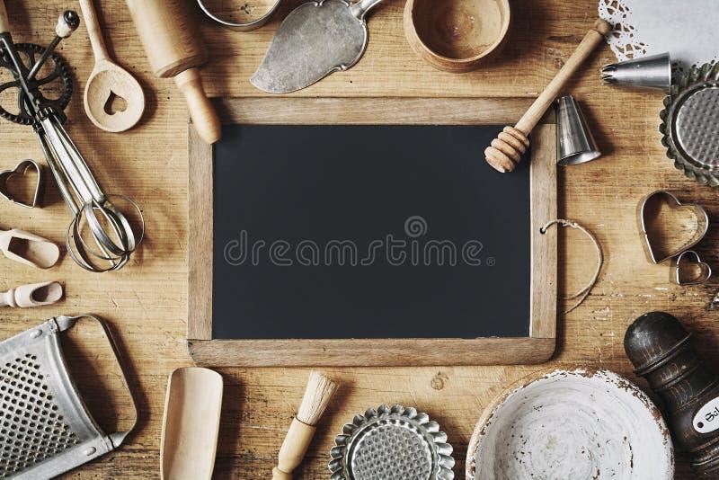 Ardósia da velha escola cercada pelo kitchenware do vintage fotos de stock