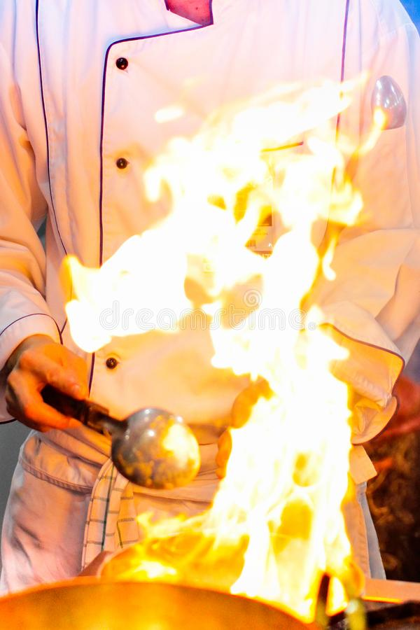 Arda o cozimento, queimadura do fogo está cozinhando na bandeja do ferro, cozinheiro chefe no restaur imagens de stock royalty free