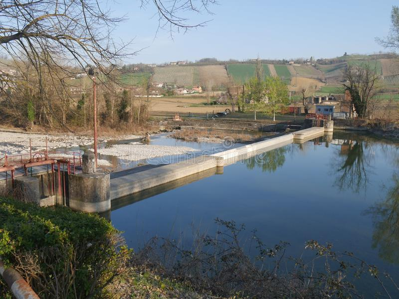 Arda river in Castell`Arquato. Small dam along stock images