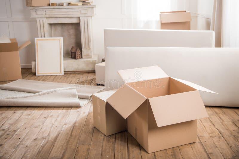 Ardboard dozen Ñ  en meubilair in lege ruimte, verhuizingsconcept royalty-vrije stock fotografie