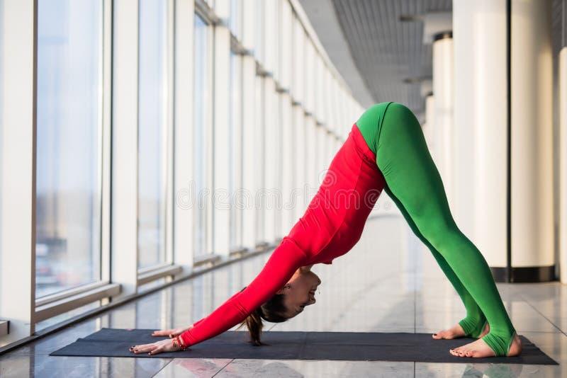 Ardha shirshasana. Beautiful yoga woman practice in a big window. Hall background. Yoga concept stock photos