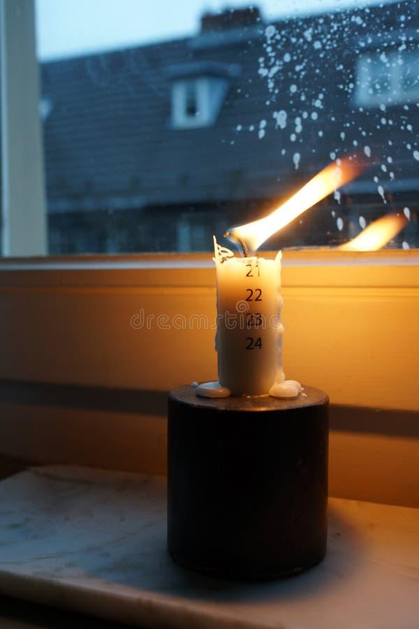 Ardiente vela de avanzada en el umbral de la ventana fotos de archivo
