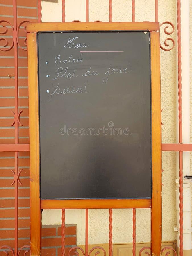 Ardoise pour écrire avec la craie le menu quotidien du restaurant en français photo stock