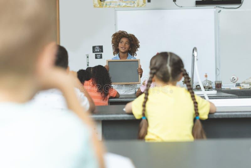 Ardoise réfléchie de participation d'écolier d'appartenance ethnique africaine dans la salle de classe photographie stock libre de droits