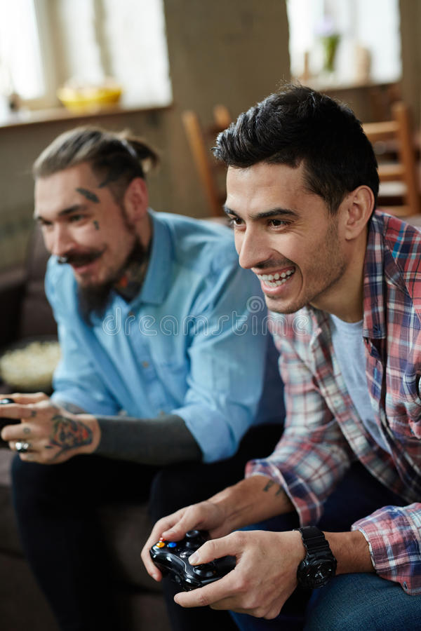 Ardor. Happy guy and his friend with joysticks playing video game royalty free stock images