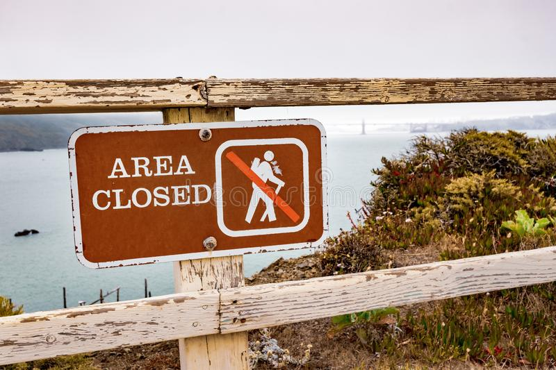 Area Closed sign posted on the Pacific Ocean coast in Marin Headlands, Marin County; Golden Gate Bridge engulfed by fog visible in stock images