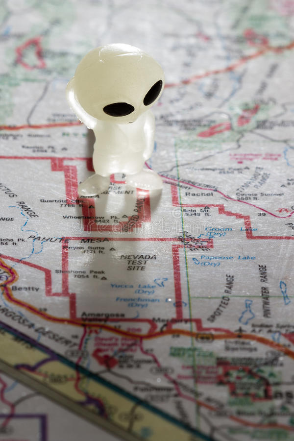 Area 51 concept. Toy ET standing on a Map of the United States, with the words Nevada test Site on the map royalty free stock photo
