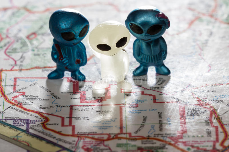 Area 51 concept. Toy ETs standing on a Map of the United States, with the words Nevada test Site on the map stock image