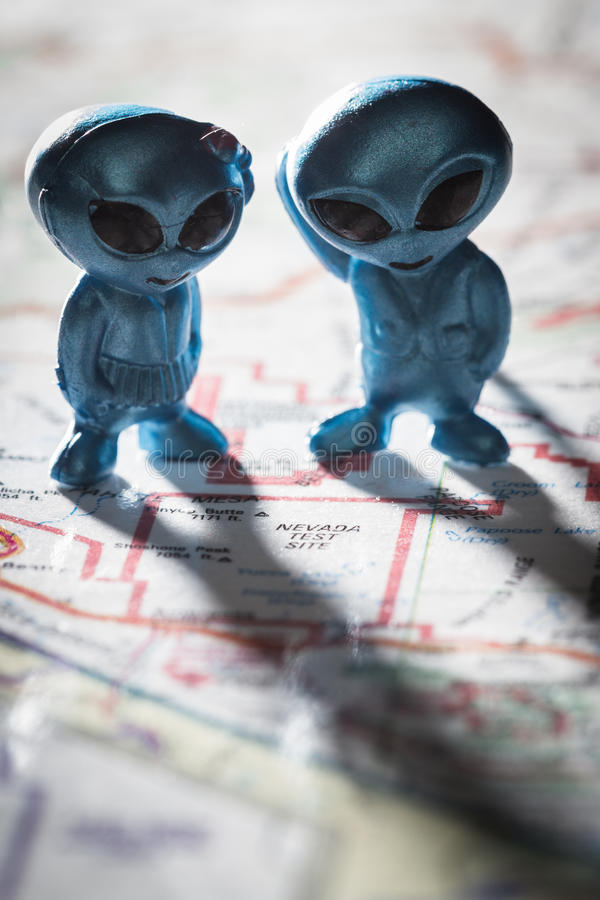 Area 51 concept. Toy ETs standing on a Map of the United States, with the words Nevada test Site on the map royalty free stock images