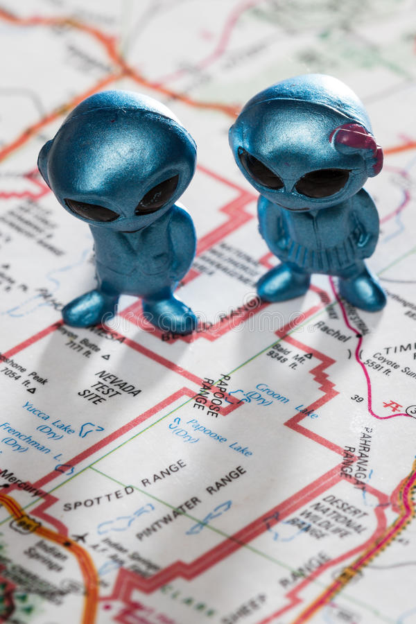 Area 51 concept. Toy ETs standing on a Map of the United States, with the words Nevada test Site on the map royalty free stock photography