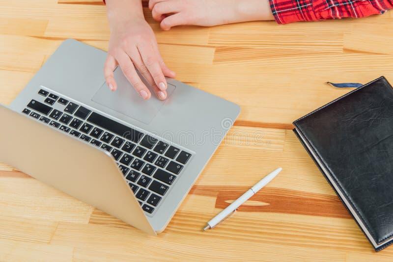 Area di lavoro con il computer portatile, le mani delle donne, il taccuino grigio, la penna bianca ed il cuscinetto nero sulla ta immagine stock libera da diritti