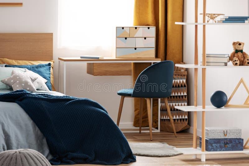 Area di lavoro con lo scrittorio e sedia nella stanza dell'adolescente elegante con progettazione blu ed arancio immagini stock