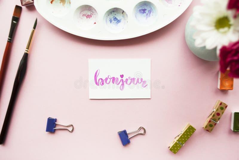 Area di lavoro dell'artista Bonjour scritto nello stile di calligrafia, tavolozza, spazzola, perno, mazzo dei fiori su un fondo r fotografia stock