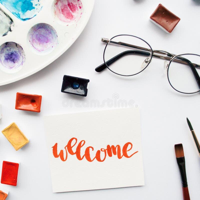 Area di lavoro dell'artista Esprima benvenuto scritto in stile di calligrafia, provette dell'acquerello e tavolozza su un fondo b fotografia stock libera da diritti