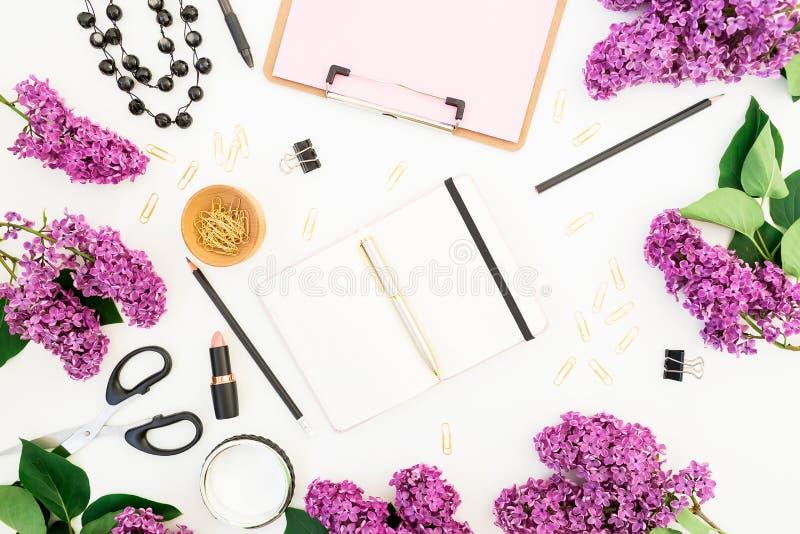 Area di lavoro di blogger o delle free lance con la lavagna per appunti, il taccuino, il rossetto, i fiori lilla e gli accessori  immagini stock libere da diritti