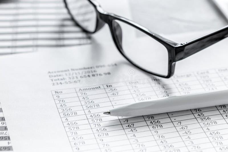 Area di lavoro di contabilità con i vetri, il profitto e le tavole sulla fine di pietra dello scrittorio su fotografie stock
