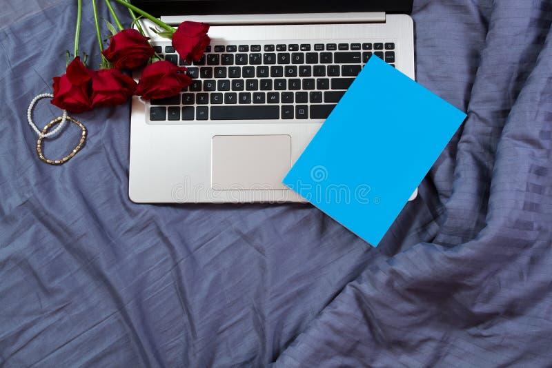 Area di lavoro e posto di lavoro a letto con Internet ed il computer portatile al fondo della camera da letto Rose e taccuino dei fotografia stock