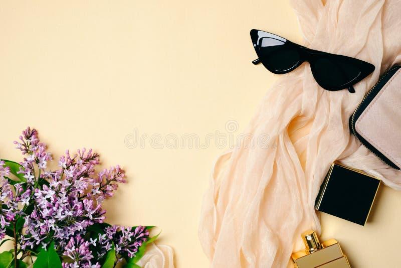 Area di lavoro femminile dello scrittorio con la sciarpa di seta, la bottiglia di profumo, gli occhiali da sole, gli accessori de immagini stock