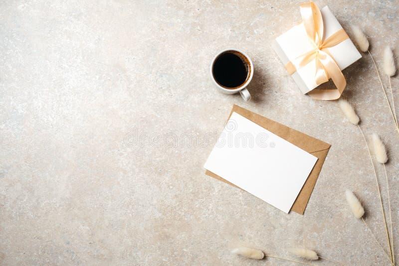 Area di lavoro minima dello scrittorio del Ministero degli Interni con la carta di carta in bianco, busta di Kraft, tazza di caff immagine stock