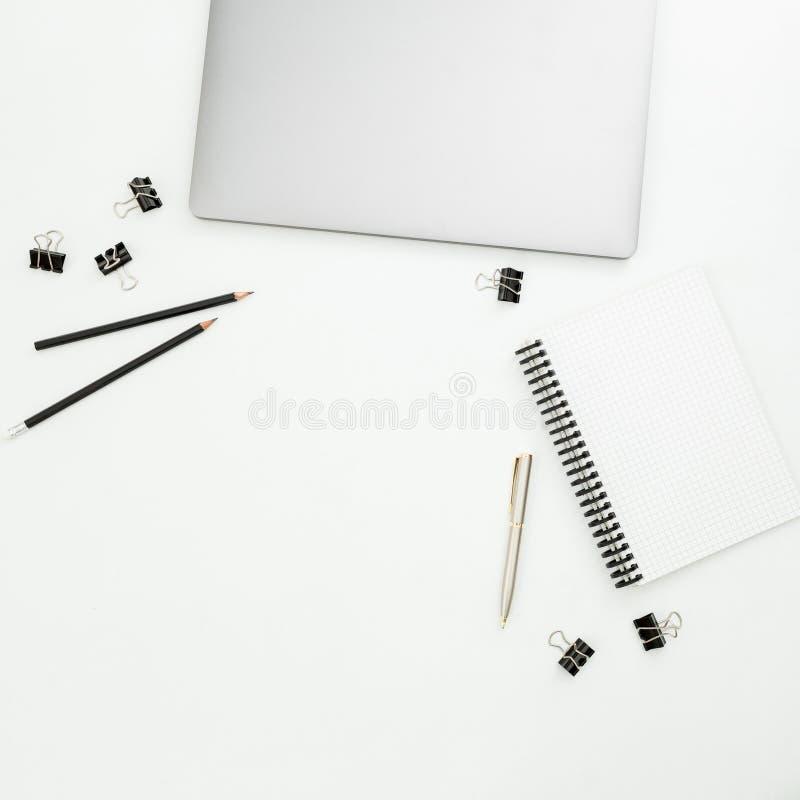 Area di lavoro moderna dell'ufficio con il computer portatile, il taccuino e gli accessori su fondo bianco Vista superiore Dispos fotografie stock