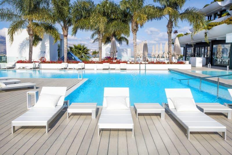Area di piscina con i letti bianchi del sole alla località di soggiorno moderna immagini stock