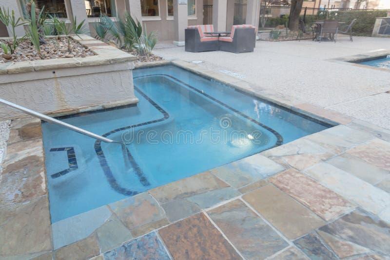 Area di riposo dello stagno e della piscina della Jacuzzi al complesso condominiale dentro fotografia stock