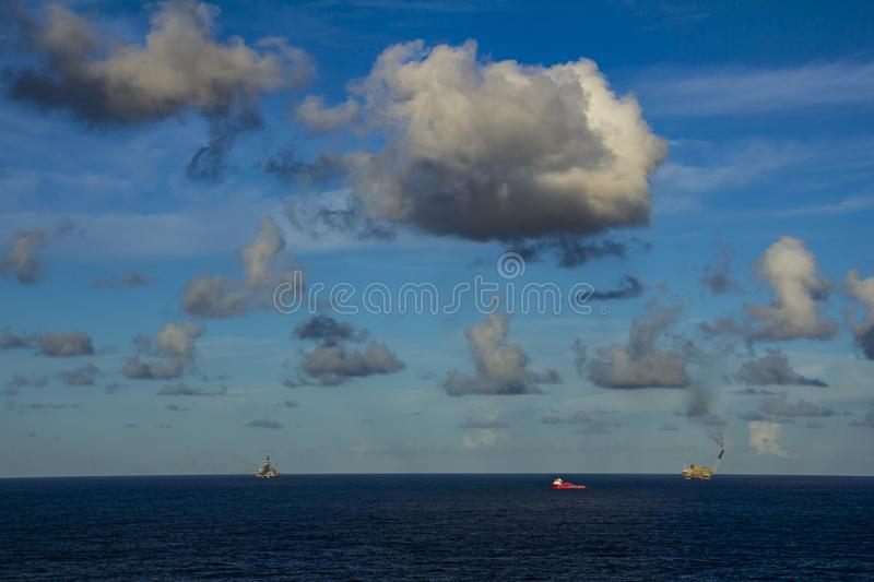 Area of work offshore on the high seas, the oil industry and a beautiful day and sunset, platform. Area of work offshore on the high seas, the oil industry and a royalty free stock image