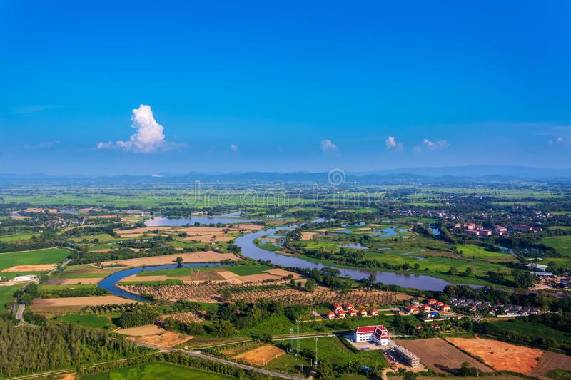 Areal shot of rural village in Chiangrai with the river Kok in and bright blue sky over. Areal shot of rural village in Chiangrai with the river Kok in and stock photography