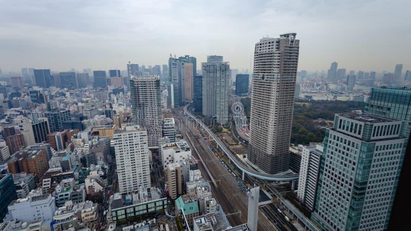Areal widok ruchliwie Tokio miasto pokazuje zwartych highrise budynki, taborowych ślada i autostrady z tła niebem, zdjęcia royalty free