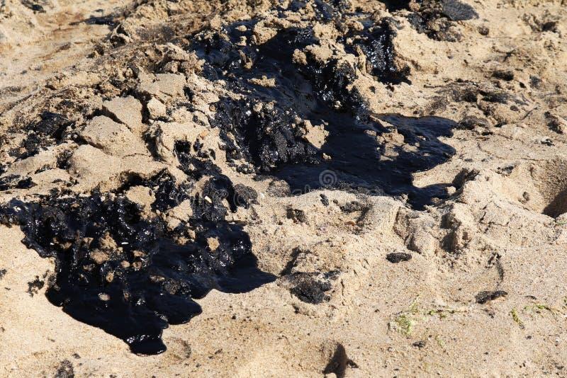 A areia é coberta com o petróleo na costa fotos de stock royalty free