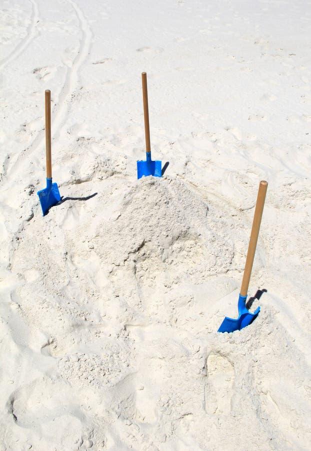 Areia branca brilhante na praia com as três pás para fazer castelos da areia em um dia de relaxamento foto de stock royalty free