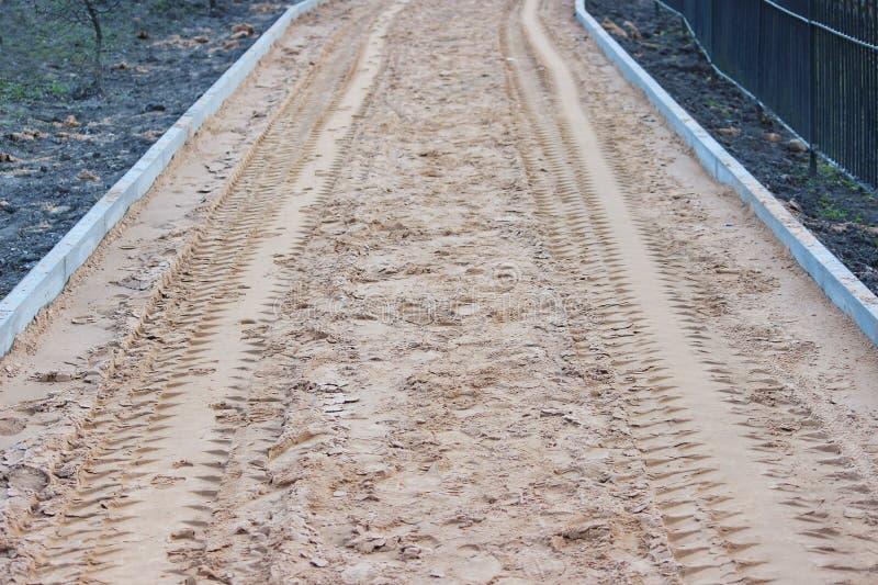 Areia como uma base antes de colocar os pavimentos, dispersados pelos trabalhadores que usam pás e tamped com um vibroroller fotografia de stock