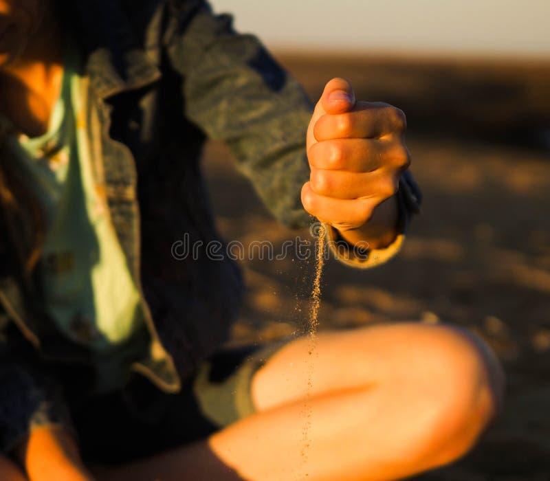 Areia da menina em seu handsn imagem de stock royalty free