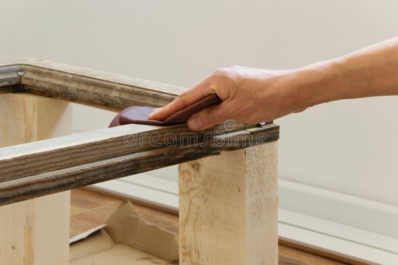 Areia da mulher com lixa fina uma tabela de madeira interna imagens de stock royalty free
