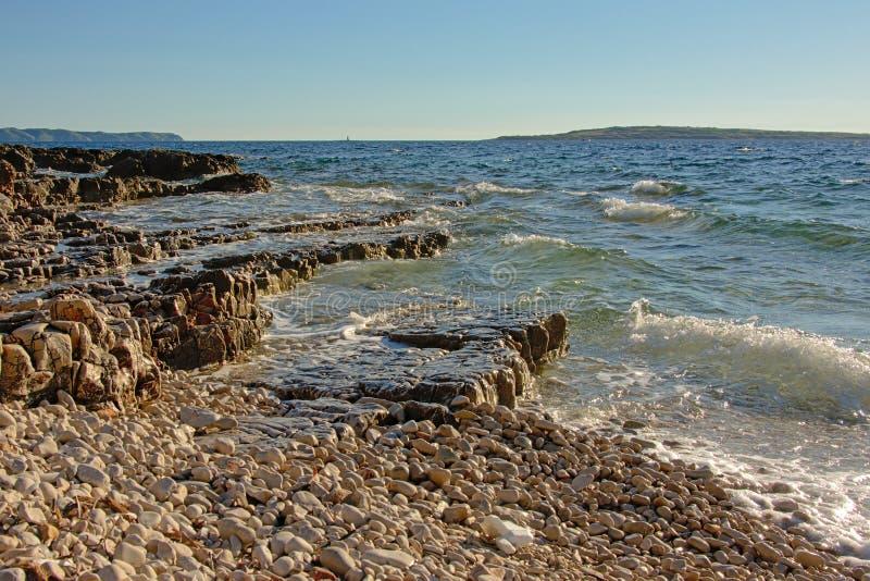 A areia da rocha vulcânica cobbles na costa do mar de adriático imagem de stock royalty free