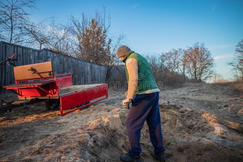 Areia das cargas do homem com uma pá no reboque do motoblock fotografia de stock