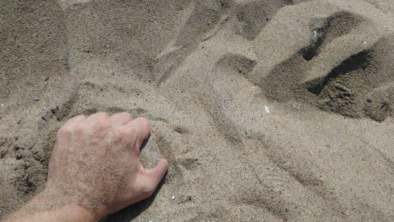 Areia de agarramento da mão em um dia ensolarado imagem de stock royalty free
