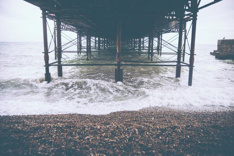 Areia de Brown ao lado do litoral e da onda da água durante o tempo do dia foto de stock royalty free